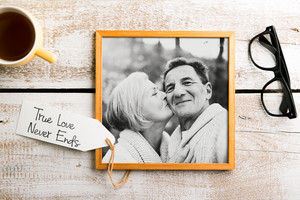 Black-and-white photo of senior couple in love in brown picture frame. Eyeglasses and cup of coffee laid on table. Studio shot on white wooden background.