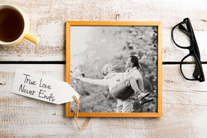 Black-and-white photo of senior couple in love in brown picture frame. Eyeglasses, cup of coffee and tag with True love never ends sign. Studio shot on white wooden background.
