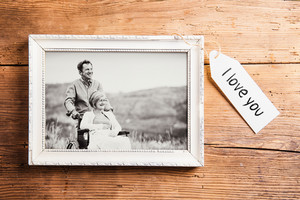 Black and white photo of senior man pushing his wife on wheelchair. Tag with I love you sign attached to it. Studio shot on brown wooden background.