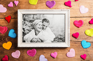 Black and white photo of seniors in autumn nature, colorful fabric hearts surrounding it. Studio shot on brown wooden background.