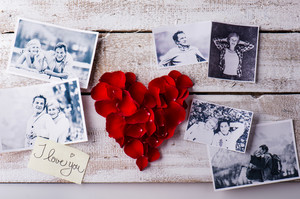 Black and white photos of a romantic senior couple laid on white wooden table. Red rose petal heart. Valentines day composition.
