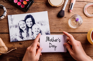 Black-and-white picture of mother hugging her daughters and various make up products. Hands of unrecognizable woman holding Mothers Day card. Studio shot on wooden background.