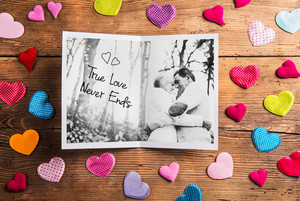 Black and white picture of senior couple in love in autumn nature, colorful fabric hearts surrounding it. Studio shot on wooden background.