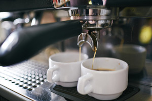 Black coffee pouring in two porcelain cups in coffee machine