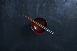 Black color wooden table top view. On the table are the Japanese chopsticks, bowl.