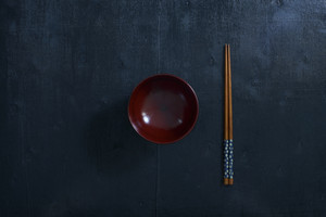 Black color wooden table top view. On the table are the Japanese wooden  chopsticks, bowl.