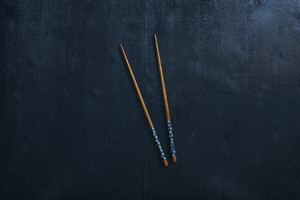 Black color wooden table top view. On the table are the Japanese wooden  chopsticks.