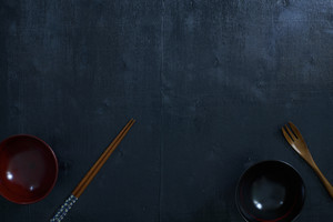 Black color wooden table top view. On the table are the Japanese wooden spoon, chopsticks, bowl.