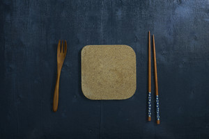 Black color wooden table top view. On the table are the Japanese wooden spoon, chopsticks.