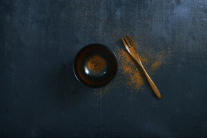 Black color wooden table top view. On the table are the Japanese wooden spoon,bowl and chili powder.