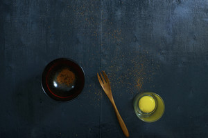Black color wooden table top view. On the table are the Japanese wooden spoon,bowl,fresh raw eggs and chili powder.