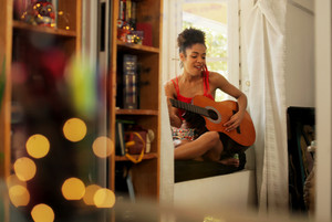 Black girl lying on couch and singing song, young african american woman relaxing. Happy latina sitting on sofa and playing guitar. Hispanic people and lifestyle. Music, leisure and relaxation at home