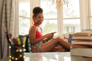 Black girl lying on couch and using smartphone, young african american woman relaxing with mobile phone. The girl is sitting on sofa, looking at camera and texting message with telephone