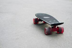 Black plastic skateboard with red wheels on asphalt close-up