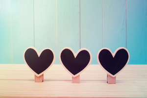 Black wooden heart shaped clothespins on vintage blue wood