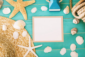 Blank message card with sea shells and straw hat on light blue wooden background