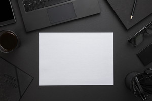 Blank Paper With Laptop And Office Supplies On Gray Desk