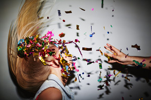 Blond girl dancing in nightclub while man throwing confetti at her