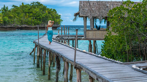 Blond Girl Staying on Wooden Pier of an Homestay looking into blue ocean, Gam Island, West Papuan, Raja Ampat, Indonesia