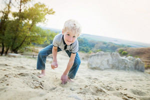 Blond little boy playing barefoot on sand beach. Warm spring day.