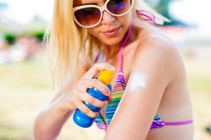 Blond woman in bikini and sunglasses putting on sunscreen on her shoulders. Sunbathing in summer.