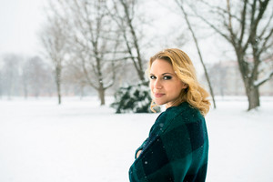 Blond woman in checked sweater outside in winter nature, snowy day