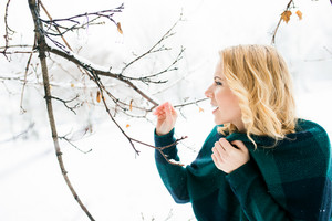 Blond woman in checked sweater outside in winter nature, tree branch, snowy day
