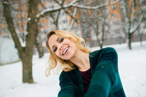 Blond woman in checked sweater taking selfie outside in winter nature