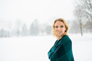 Blond woman in checked sweater throwing her hair outside in winter nature