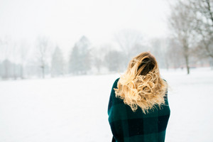 Blond woman in checked sweater throwing her hair, winter nature, back view, rear viewpoint
