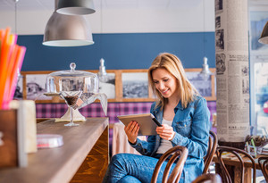 Blond woman in denim shirt sitting at the bar in modern city cafe, holding a smart phone, texting