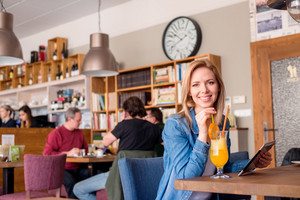 Blond woman in denim shirt sitting in modern city cafe with drink, holding tablet
