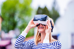 Blond woman in striped sweatshirt wearing virtual reality goggles in the street