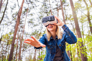 Blond woman wearing virtual reality goggles outside in green forest, spring nature