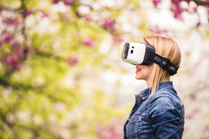 Blond woman wearing virtual reality goggles outside in spring nature