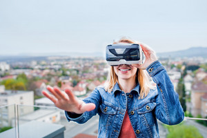 Blond woman wearing virtual reality goggles standing on a balcony
