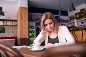 Blond woman with newspaper in cafe sitting at the table drinking coffee