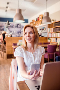 Blond woman with smart phone in modern city cafe sitting at the table working on notebook