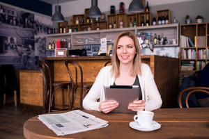 Blond woman with tablet in cafe sitting at the table drinking coffee