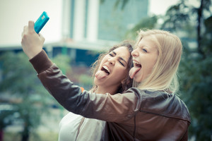 blonde and brunette beautiful stylish young women selfie in the city