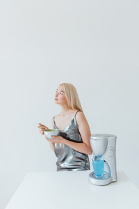 Blonde fashion glamour girl in silver shiny dress holding bowl and standing at the table isolated on the grey background