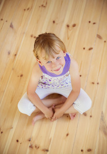 Blonde girl sitting on the wooden floor in house
