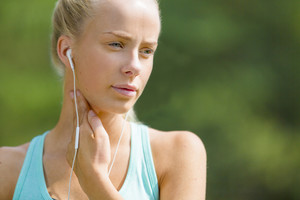 Blonde woman checking her pulse after a long run