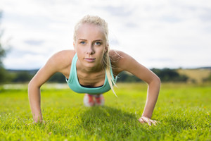 Blonde woman doing push-ups in the park