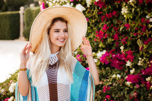 Blonde Woman in beachwear and hat which posing near the flower bush