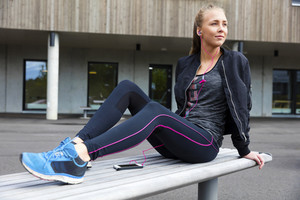 Blonde woman in workout outfit sits outdoor and uses phone
