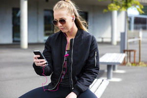 Blonde woman with sunglasses sits outdoor and uses phone