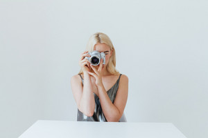 Blonde young woman making photo with camera while sitting at the white table isolated on the grey background