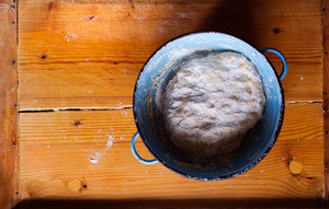 Blue bowl with dough. Studio shot on wooden background.