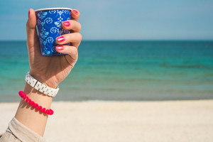 Blue cup of coffee with an ornament in the left female hand against the background of the beach. On the women's hand red and white bracelets. On nails red manicure.
